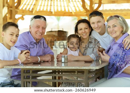 Happy family  at table outdoors in summer time - stock photo