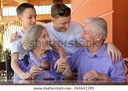 Happy family at table outdoors in summer time