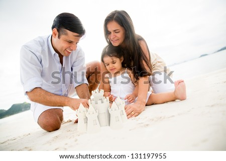 Happy family at the beach making sand castles - stock photo