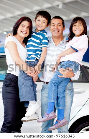 Happy family at the dealer buying a new car - stock photo