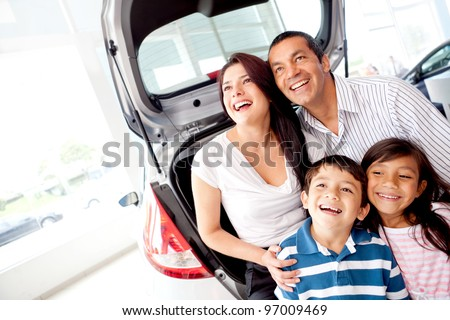 Happy family at the dealership buying a car - stock photo