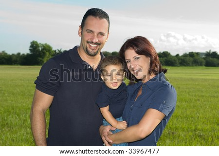 Happy Family at the Park Smiling at the Camera - stock photo