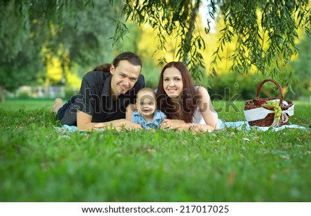 Happy family at the picnic in the park - stock photo