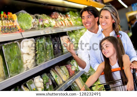 Happy family at the supermarket buying groceries - stock photo