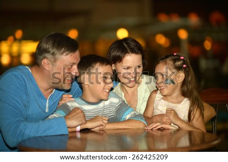 Happy family at the table in the evening - stock photo