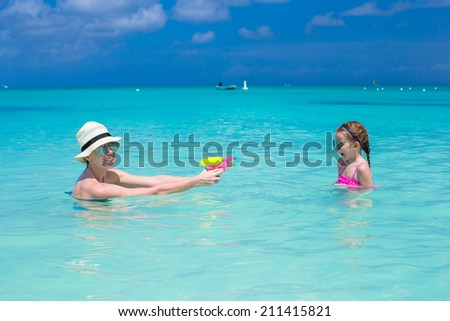 Happy family at tropical beach having fun - stock photo