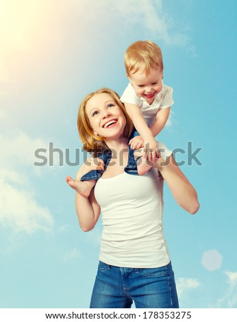 happy family. baby sits astride the shoulders of the mother and laughing on blue sky background - stock photo