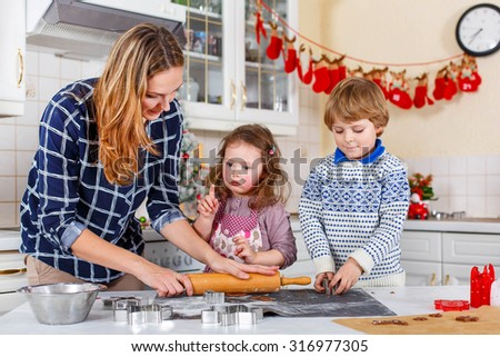 Happy family baking Christmas cookies at home. Woman, little son and daughter having fun in domestic decorated kitchen. Traditional leisure with kids on Xmas - stock photo