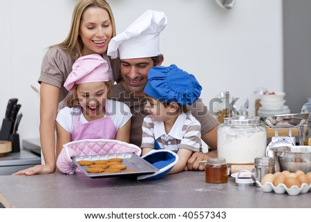 Happy family baking cookies together in the kitchen - stock photo