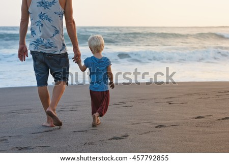 Happy family - barefoot father holds baby son hands, walk with fun along sunset sea surf on black sand beach. Travel, active parents lifestyle, people activity on summer vacations with children.