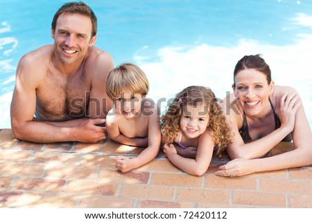 Happy family beside the swimming pool - stock photo
