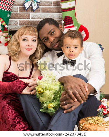Happy family: black father, mom and baby boy by fireplace. Christmas and New Year - stock photo