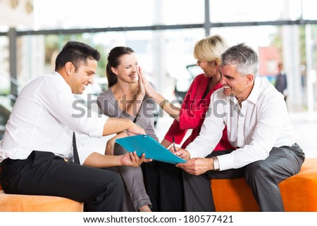 happy family buying a new car at vehicle showroom - stock photo