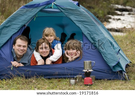 Happy family camping in tent - stock photo