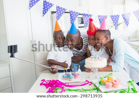 Happy family celebrating a birthday together and taking a selfie at home in the kitchen
