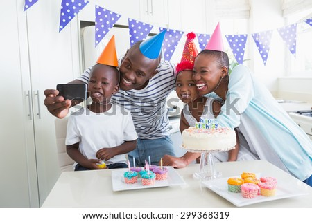 Happy family celebrating a birthday together and taking a selfie at home in the kitchen - stock photo