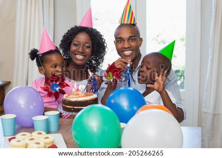 Happy family celebrating a birthday together at table at home in the kitchen - stock photo