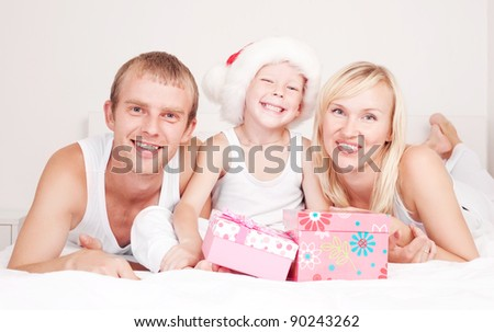 happy family celebrating Christmas and opening presents, on the bed at home - stock photo