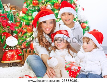 Happy family celebrating Christmas at home, mother with three cute kids wearing red Santa hat, happiness and enjoyment concept