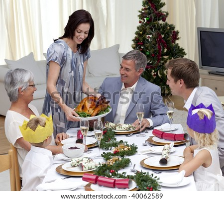 Happy family celebrating Christmas dinner with turkey at home - stock photo