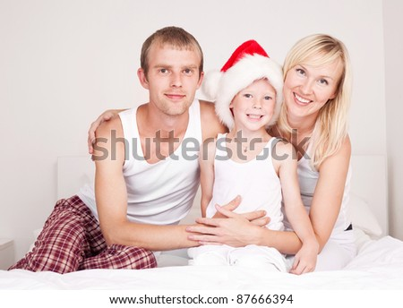 happy family celebrating Christmas: mother ,father and their son on the bed at home - stock photo