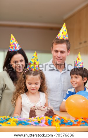 Happy family celebrating daughters birthday together - stock photo