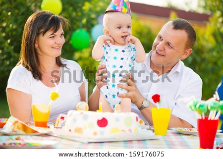 Happy family celebrating first birthday of baby son