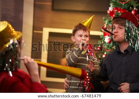 Happy family celebrating new year's eve together, wearing funny hat and blowing horn. - stock photo