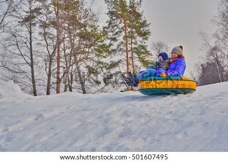 Happy family & children enjoying a winter sleigh ride on a winter slope