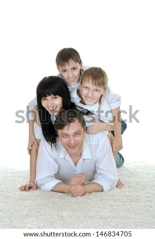 Happy family climbing on top of each other on the floor
