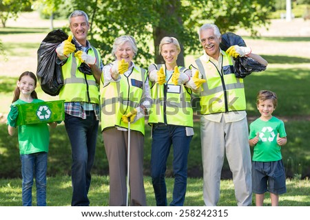 Happy family collecting rubbish with thumbs up on a sunny day - stock photo
