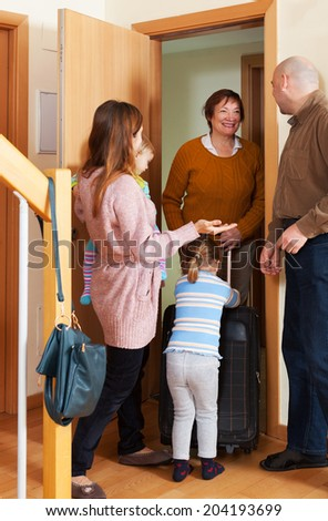 Happy family coming to grandmother home - stock photo