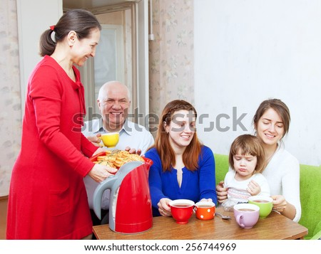 happy  family communicate over tea with cakes at home - stock photo