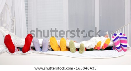 Happy family concept. Feet of father, mother and four children in colorful knitted socks on white bed. Family sleeping together. - stock photo