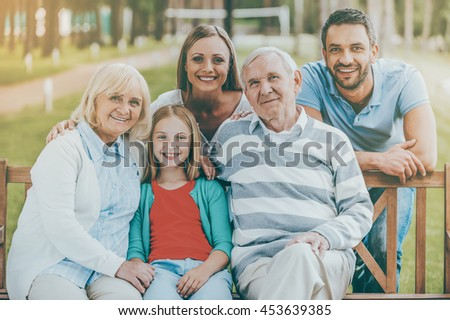 Happy family concept. Happy family of five people bonding to each other and smiling while sitting outdoors together - stock photo