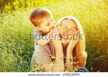 "Happy family concept. Mother and her child son enjoying summer and playing a game "" Guess Who "" on the grass and smiling. Sunny summer weather. Close up. Outdoor shot - stock photo"
