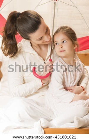 Happy family concept. Mother and her little lovely daughter, concept of togetherness. Mother embracing her beautiful little girl while sitting on the bed under umbrella, concept of security - stock photo