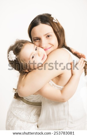 Happy family concept. Mother and her little lovely daughter, concept of togetherness, studio shot. Happy Mother hugging her little pretty girl on white background. - stock photo