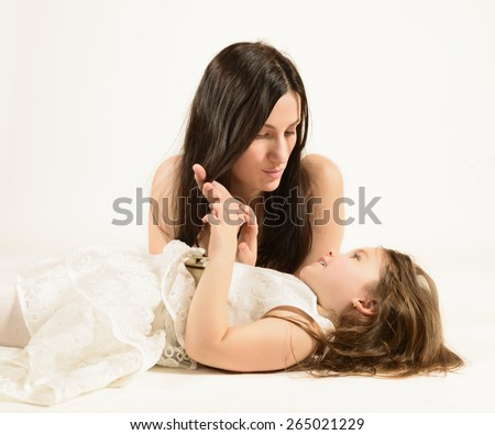 Happy family concept. Mother and her little lovely daughter, concept of togetherness, studio shot. Mother looking with love at her beautiful little girl. - stock photo