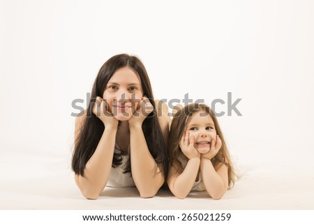 Happy family concept. Mother and her little lovely daughter, concept of togetherness, studio shot. Mother and daughter having fun posing, studio shot on white background - stock photo