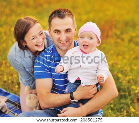 Happy family concept. Parents  and lovely daughter at summer field.