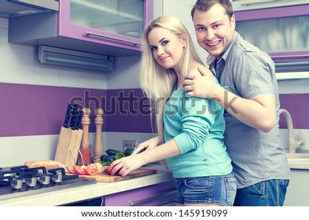 Happy family concept. Portrait of a romantic couple (husband and wife) standing together in their new kitchen room and preparing breakfast. Woman is pregnant. Healthy food. Indoor shot - stock photo