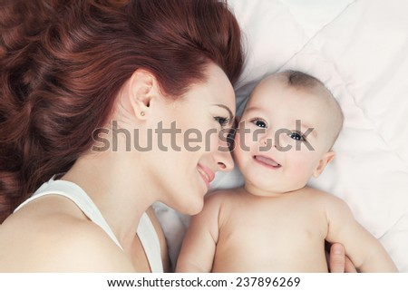 Happy family concept. Young mother and her baby smiling and hugging over white blanket. - stock photo