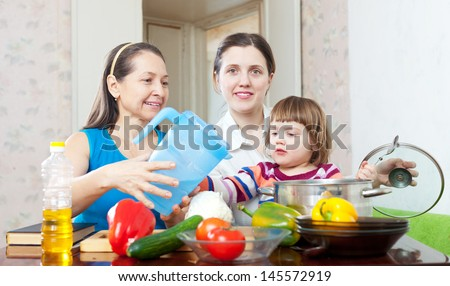 Happy family cook  with vegetables in the kitchen at home