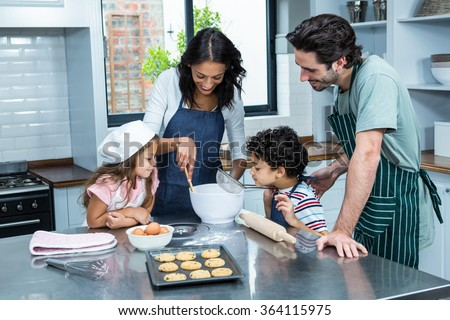 Happy family cooking biscuits together in kitchen at home - stock photo