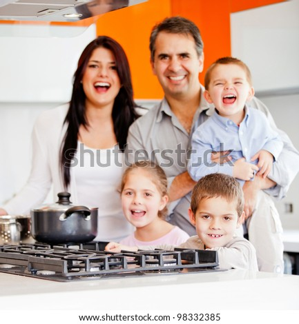 Happy family cooking dinner at home and smiling
