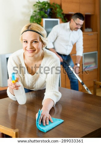 Happy family couple cleaning in house together and smiling - stock photo