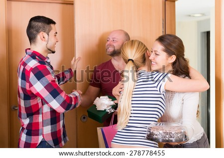 Happy family couple receiving visitors with a gifts in the home  - stock photo