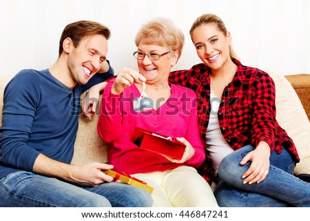 Happy family - couple with old woman who holding gift box and baby shoe
