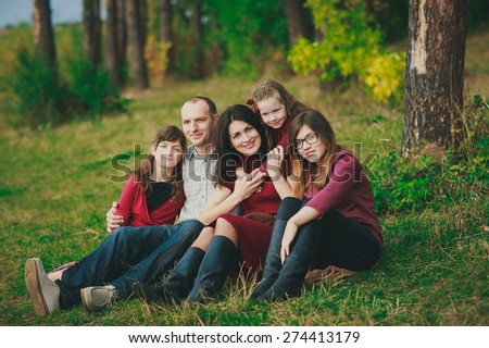 happy family couple with their three beautiful daughter on the walk in the wood  - stock photo